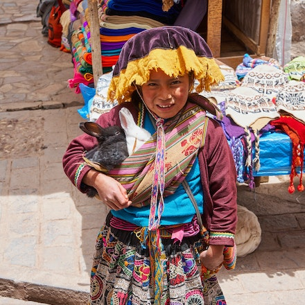 Girl with rabbits - A young local girl poses with rabbits, for some tourist money. Pisac, Sacred valley.