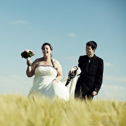 100 Simply Happy - A candid and happy moment as the bride and groom traverse the field